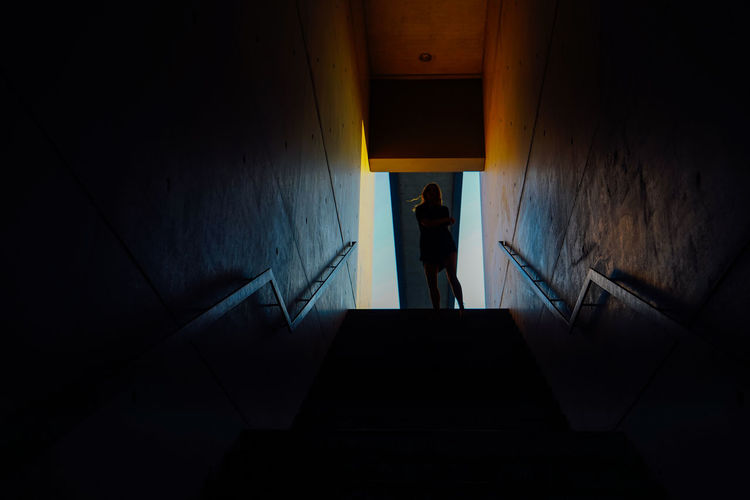 Low angle view of silhouette woman standing on steps