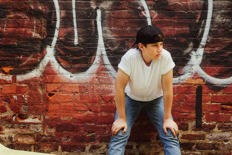 Full length of young man standing against brick wall