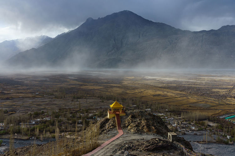 Aerial view of temple building against mountain during foggy weather