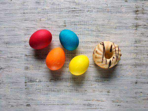 Easter colorful eggs and a cake on a white wooden background Table Egg High Angle View Indoors  No People Multi Colored Directly Above Wood - Material Easter Food Close-up Day Cake Wooden Easter White Background Handmade
