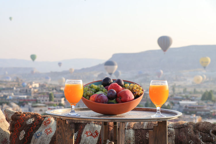 Fruits in bowl on table against sky