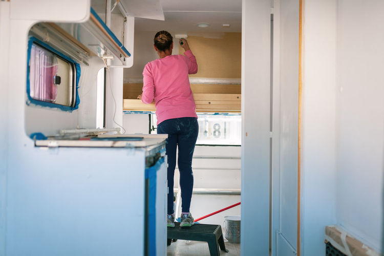 Rear view of woman painting in camper trailer