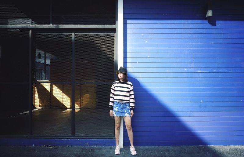 Full length of girl standing against building