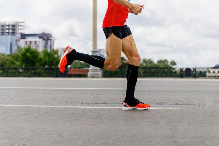 Man runner in black compression socks run city marathon