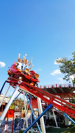 Low Angle View Of Girls With Arms Raised Sitting On Amusement Park Ride Against Blue Sky