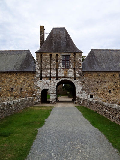 The entrance of Gratot castle, Normandy Arch Architecture Building Exterior Built Structure Chateau Gratot Cloud - Sky Day Entrance Façade Footpath France French Castle History Leading No People Normandy Outdoors Sky The Way Forward Weathered