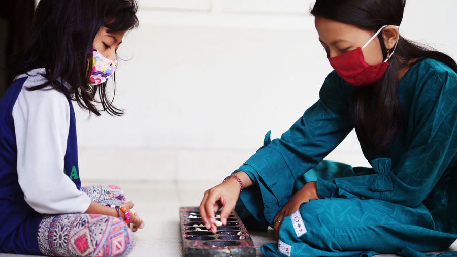 Two girls wearing masks play dakon, a traditional indonesian children's game
