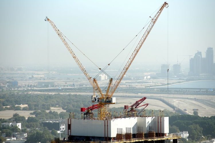 Crane in city by buildings against sky