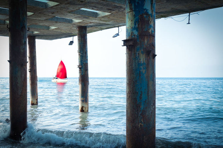 Concept of discovery, hope and travel - a sailboat with a red sail floats by the sea. View from the old pillars of the pier. Float Dream Hope Perspective Red Travel Abstract Adventure Architectural Column Beauty In Nature Boat Concept Discovery Explorer Horizon Horizon Over Water Nautical Vessel Sail Sailboat Sea Summer Tranquility Water Wonderlust Yacht #FREIHEITBERLIN