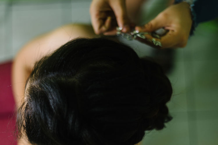 Cropped hands of hairdresser holding hair clip by bride