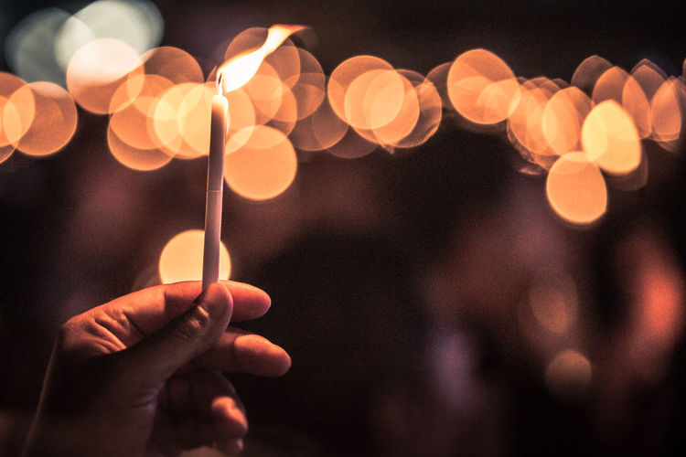 Close-Up Of Hand Holding Candle At Night