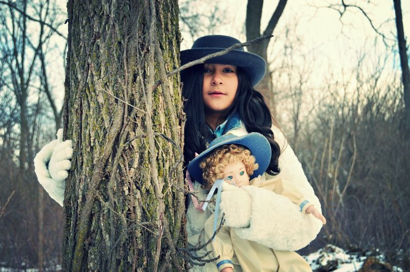 Portrait Of Teenage Girl With Doll Standing By Tree During Winter