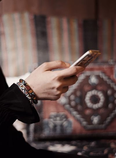 Cropped hand of woman using mobile phone