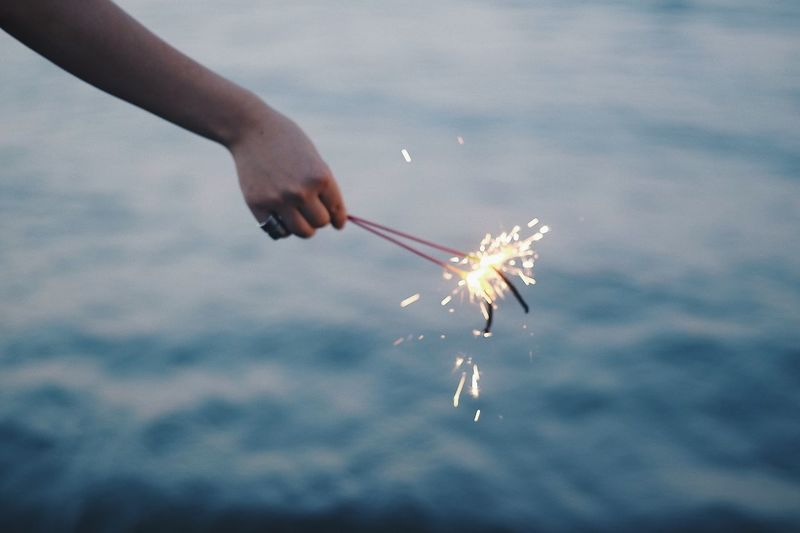 Cropped hand of woman holding illuminated sparklers against sea during sunset