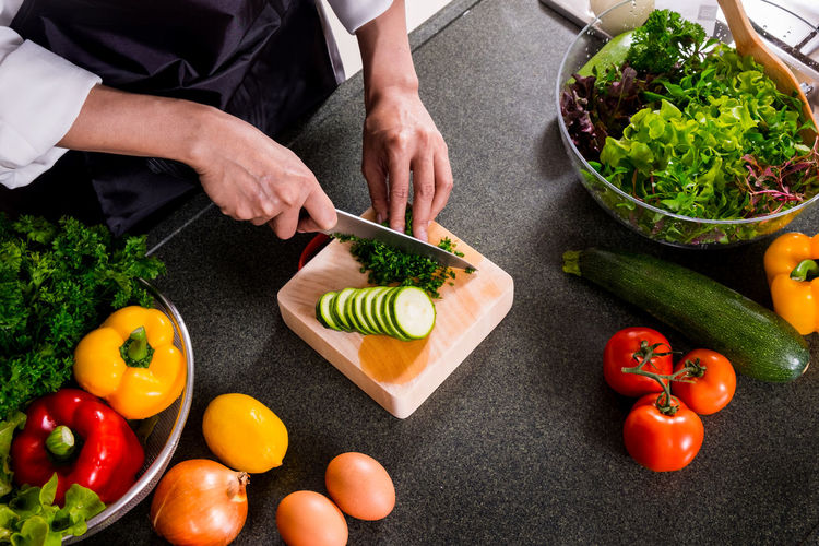 Midsection of man chopping vegetables in kitchen