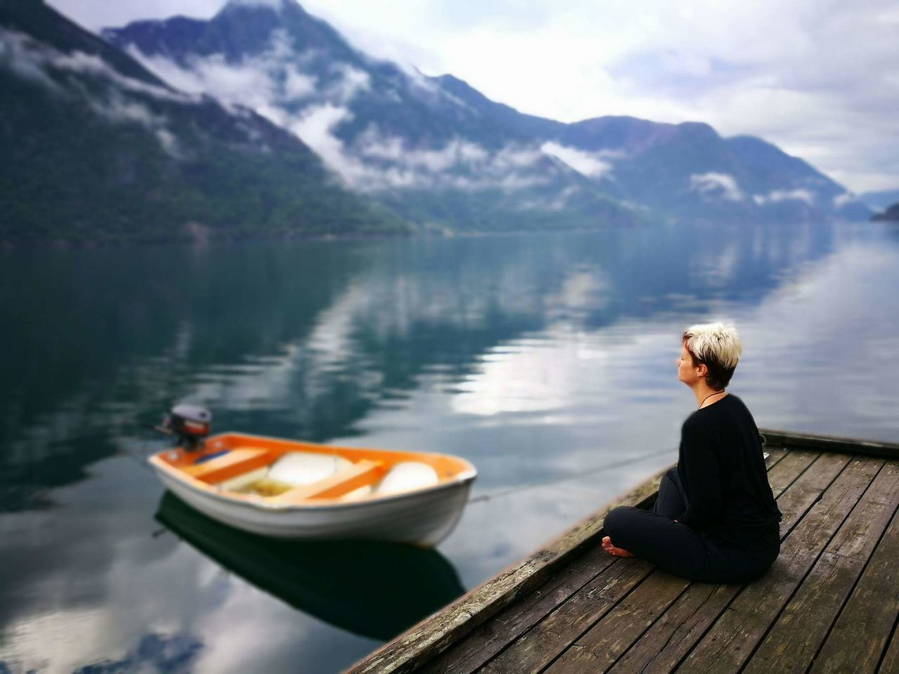 mountain, lake, water, nature, mountain range, sitting, day, rear view, nautical vessel, beauty in nature, leisure activity, scenics, outdoors, tranquility, tranquil scene, one person, real people, full length, blond hair, oar, sky, adult, tree, young adult, adults only, people
