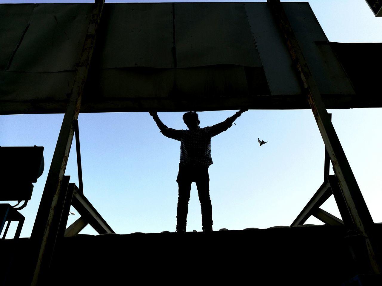 SILHOUETTE OF MEN ON BRIDGE AGAINST SKY