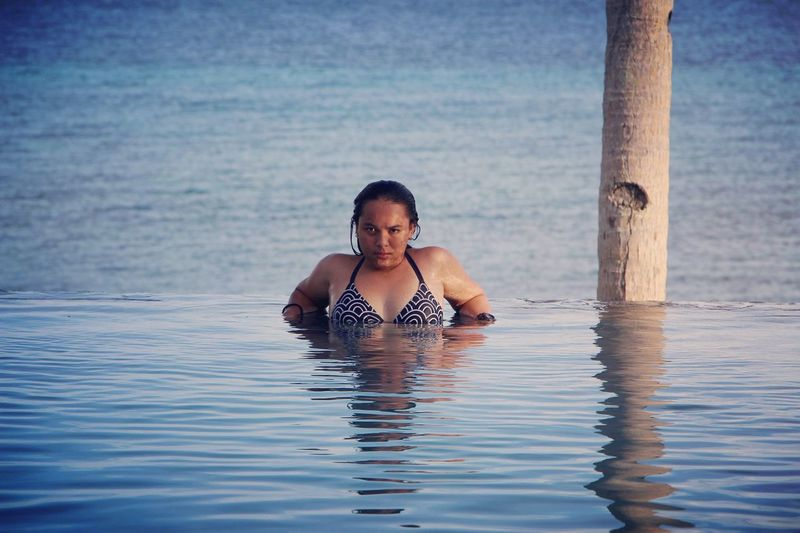 Portrait of woman swimming in infinity pool