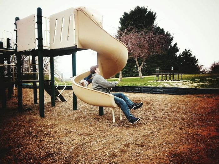 Mother And Son Enjoying Slide At Playground