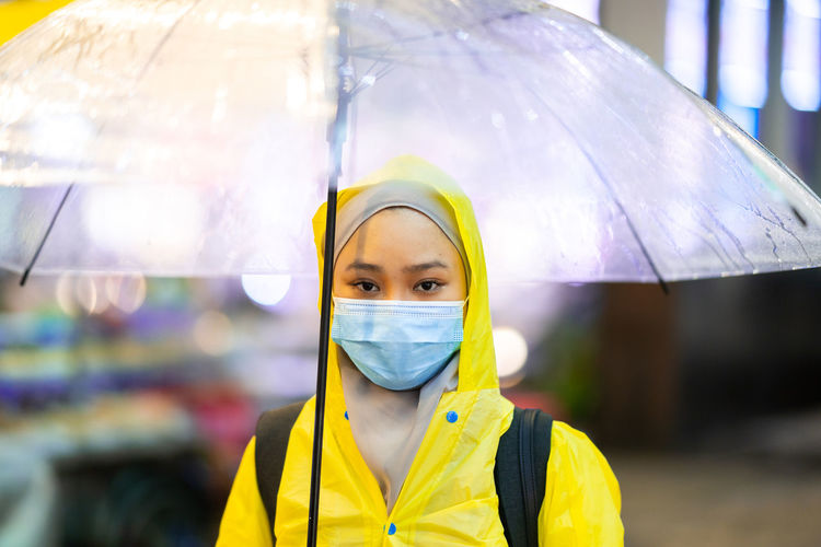 Portrait of woman with umbrella wearing mask