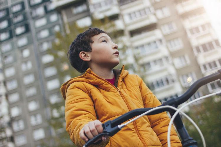 Boy cycling in car against sky