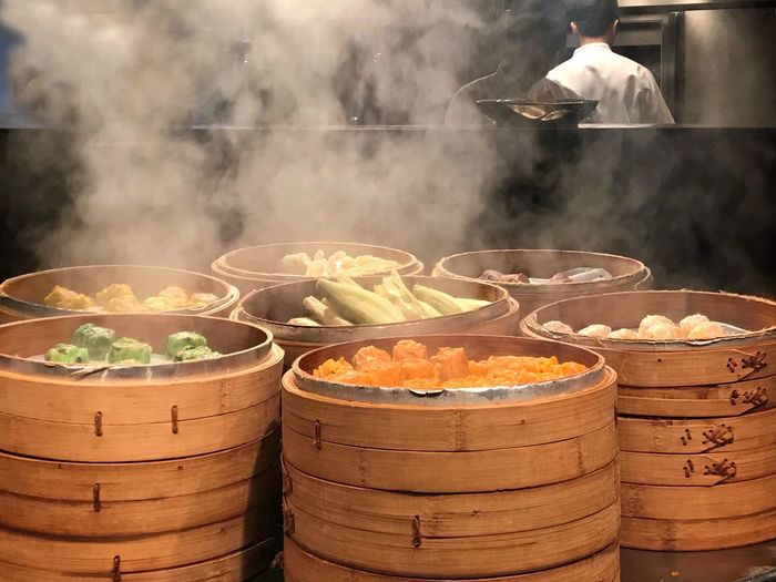 Food in bamboo steamers on table in kitchen with man in background
