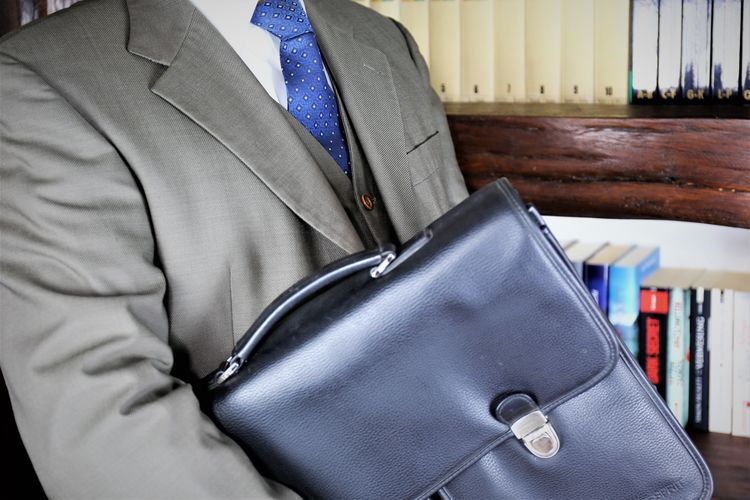 Midsection of businessman holding leather bag at office