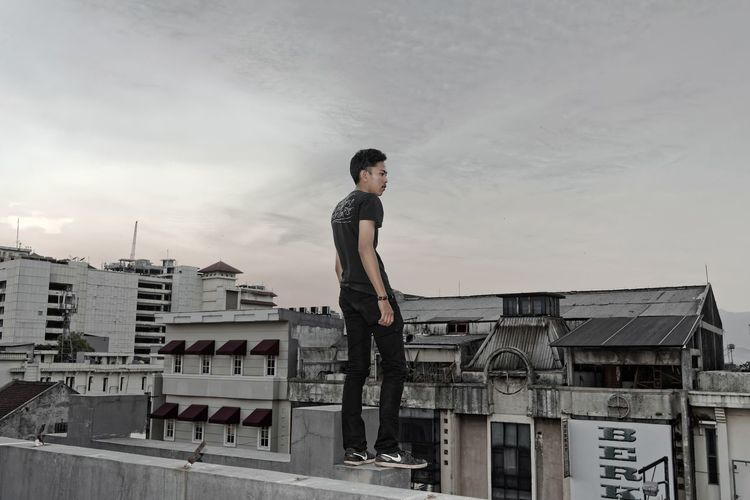Young man standing on terrace in city against sky