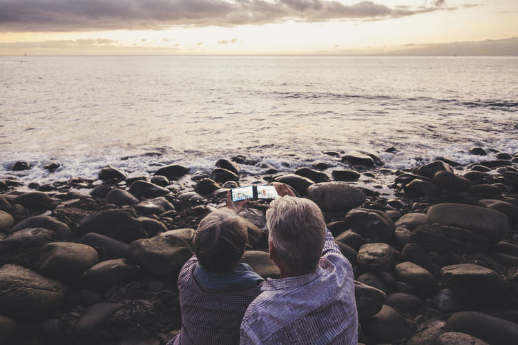 senior couple with mobile technology, ocean, sunset Beach Beauty In Nature Horizon Over Water Leisure Activity Love Nature Outdoors Real People Rear View Rock - Object Scenics Sea Senior Couple Shore Shoreline Sky Standing Sunset Togetherness Tranquil Scene Two People Water Wave