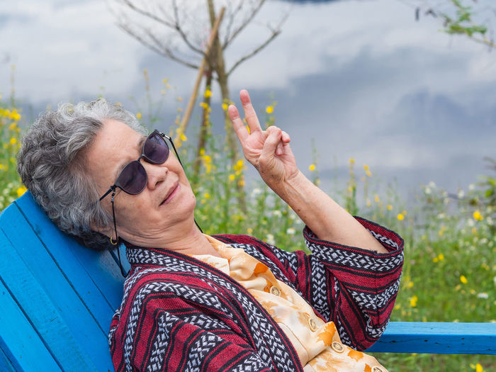 Portrait of elderly woman wearing sunglasses sitting on chair side the lake.