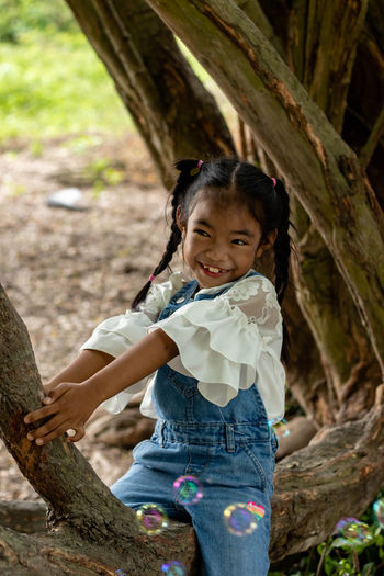 Portrait of a smiling girl sitting on tree trunk