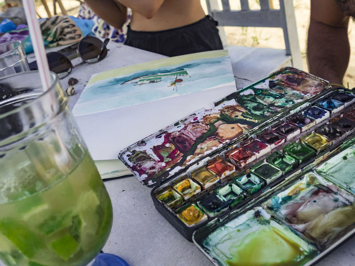 stilife with aquarel, paintbox and caipirinha under the shade Aquarell PaintBox Art And Lesure Artist In Brasil Bahia/brazil Caipirinha Coctail Food And Drink Leisure Activity Real People Stilife With Cocktail