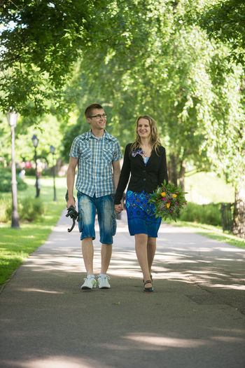 Couple holding hands while walking at park
