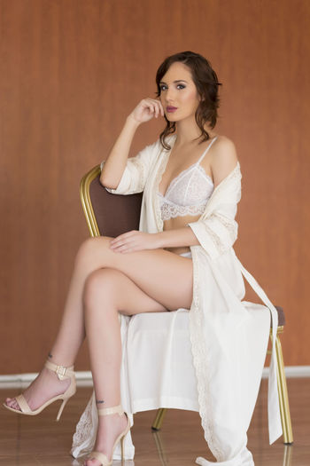 Portrait of beautiful model sitting in lingerie on chair against wall