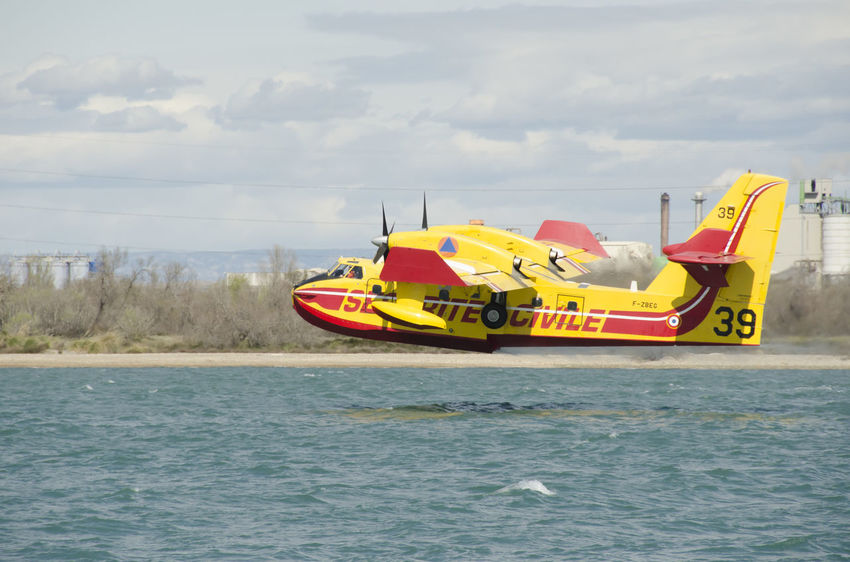 Canadair water bomber plane in training Firefighter Plane Airplane Canadair Cloud - Sky Day Flying Mode Of Transportation Motion Outdoors Scenics - Nature Sea Sky Transportation Water Water Bomber Waterfront Yellow