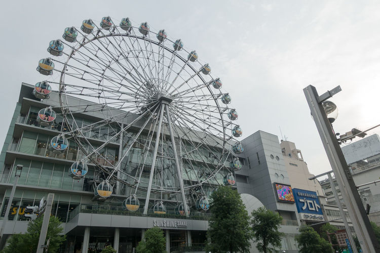 Low angle view of ferris wheel in city against sky