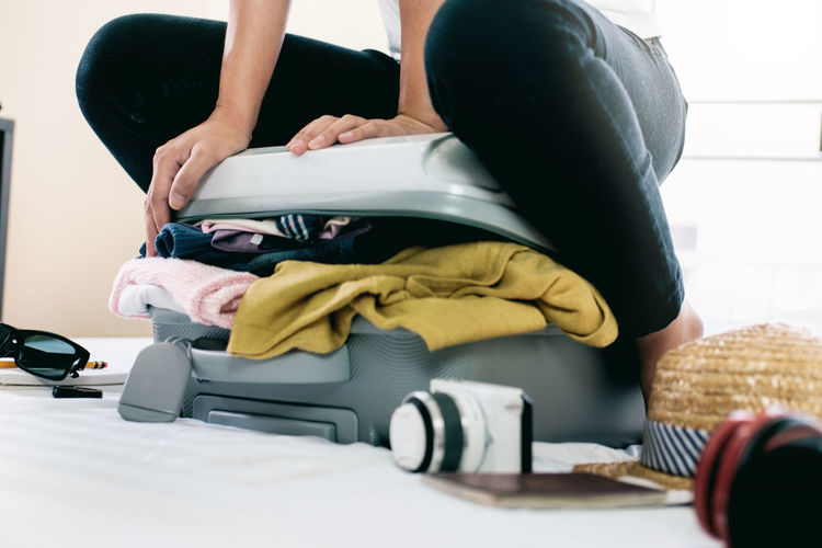 Midsection Of Woman Packing Overburdened Clothes In Suitcase