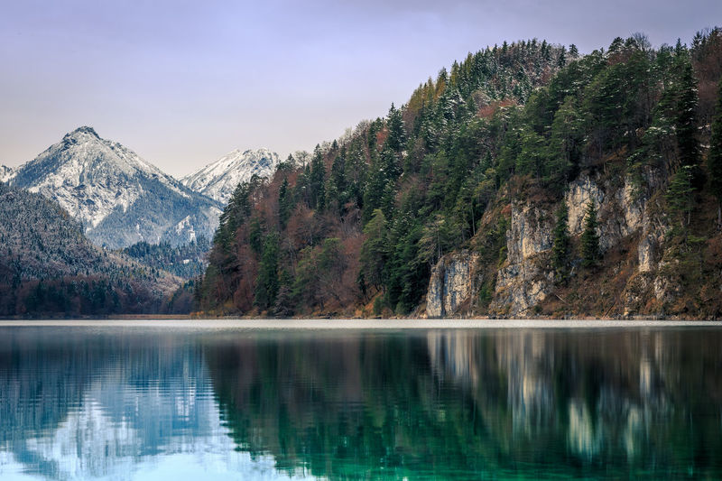 Trees and mountain reflecting on calm lake during winter
