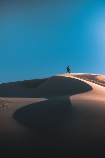 Exploring the open beauty of the sand dunes. The Great Outdoors - 2018 EyeEm Awards WeekOnEyeEm Arid Climate Blue Clear Sky Climate Copy Space Day Desert Land Landscape Leisure Activity Lifestyles Men Nature One Person Outdoors Real People Sand Sand Dune Sand Dunes Scenics - Nature Sky Travel Week On Eyeem