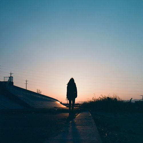 Rear View Of Woman Standing On Road At Sunset