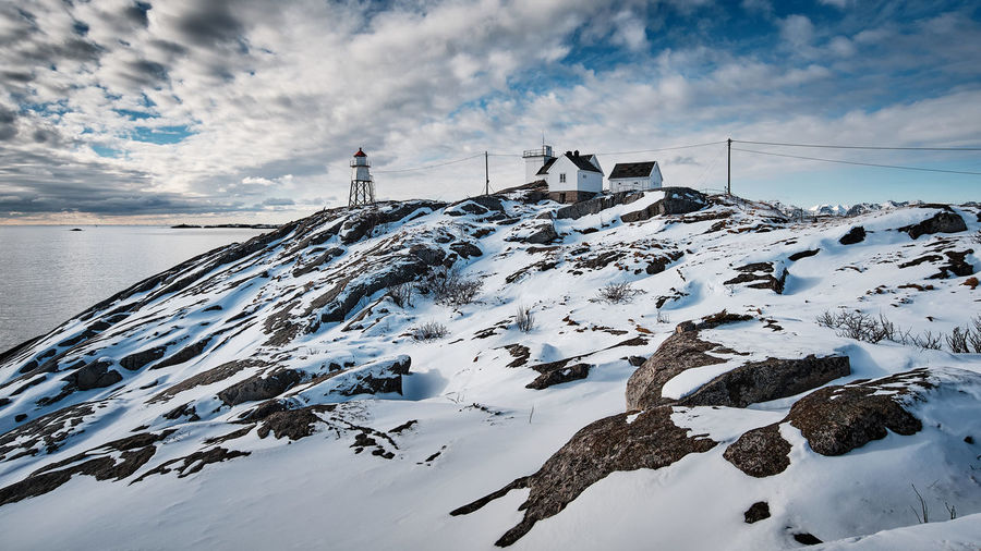 Scenic view of lighthouse on snow mountain against cloudy sky