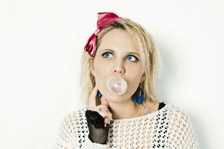 Headshot of a beautiful blond woman dressed in retro 80s costume blowing bubblegum, thinking 1980s 1980s Style 80s Beautiful Dressed Up Fashion Retro Thinking Woman Blooming Blowing Blowing A Bubble Bubble Bubble Gum Bubblegum Caucasian Costume Female Hair Style Headshot Mid Adult Woman One Person Portrait Style White Background