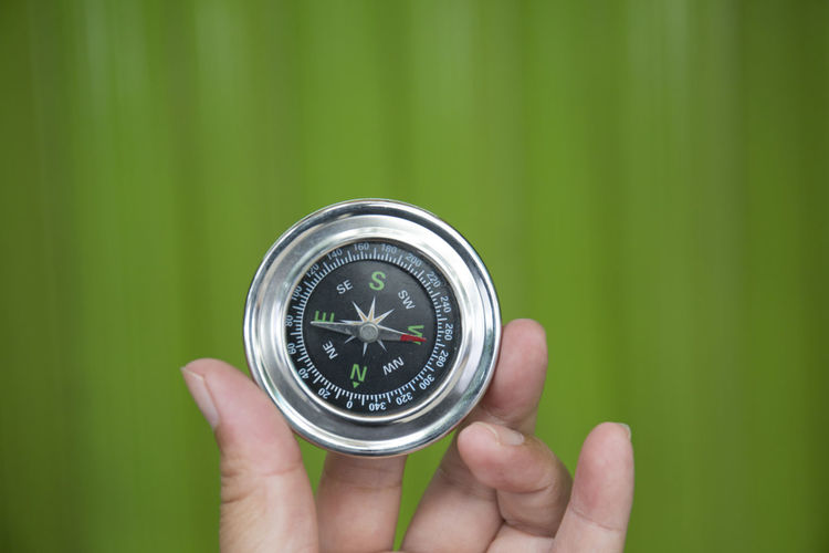 Compass on Green Background Compass Human Hand Hand Human Body Part One Person Holding Finger Human Finger Navigational Compass Body Part Direction Guidance Close-up Focus On Foreground Unrecognizable Person Exploration Discovery Real People Green Color Number Human Limb Searching Green