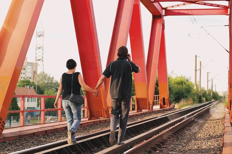 Rear view of people on railroad tracks