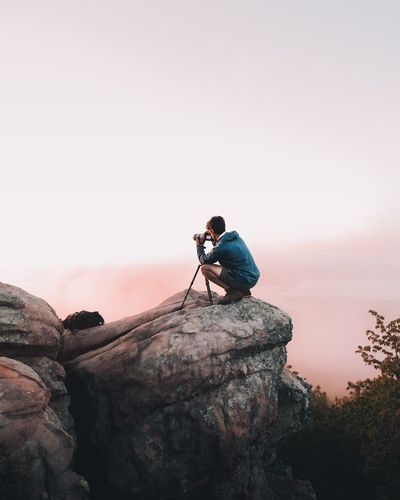 Side View Of Hiker Photographing On Cliff Against Sky During Sunset