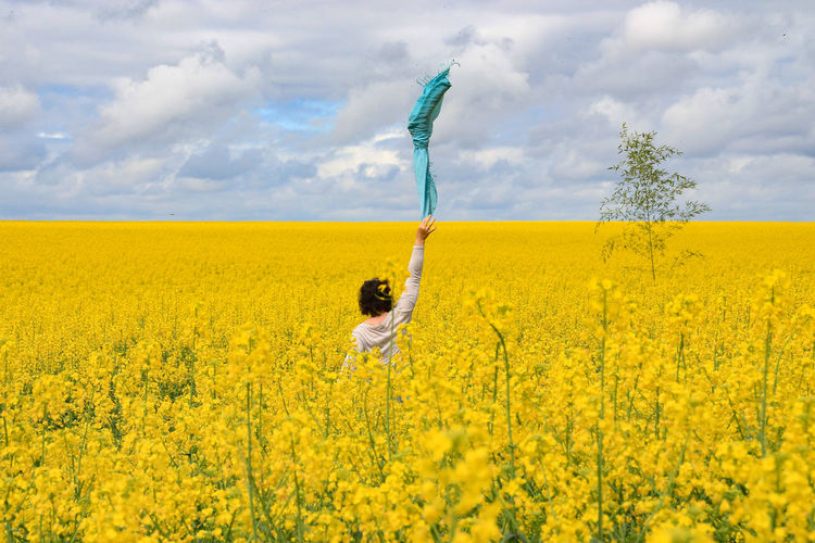 Rear view of woman throwing scarf in mid-air while standing amidst rapeseed field against cloudy sky