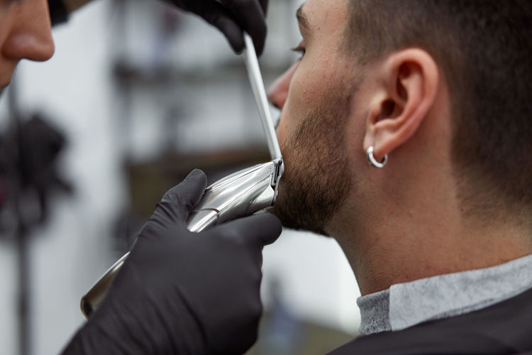 Close-up of man sitting in barber shop