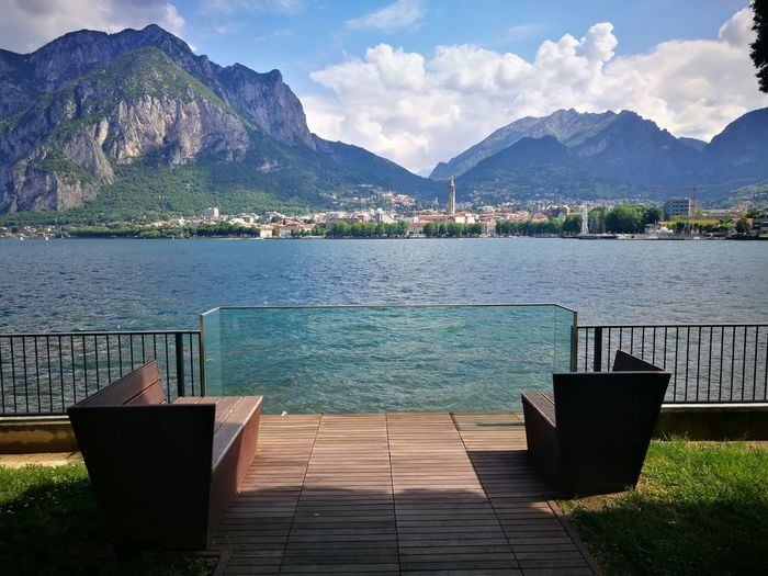 Chairs by swimming pool against lake and mountains