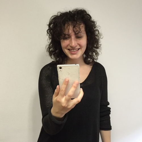 Smiling young woman using phone against wall