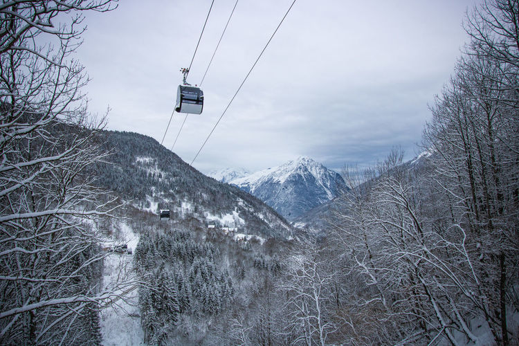 Snow covered mountain and cable car against sky